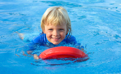 Happy  little boy has fun with floating board  in  swimming pool