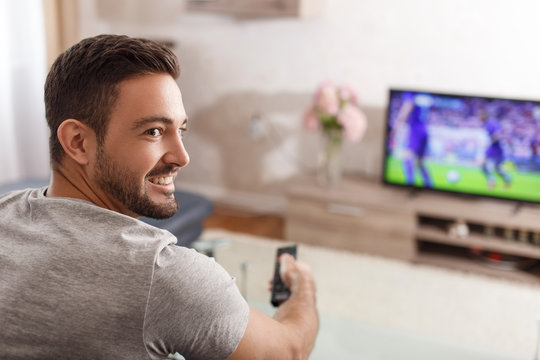 Excited man switch TV to soccer