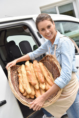 Cheerful baker delivering bread to client