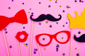 Photo booth props glasses, mustache, crown, lips on a pink background flat lay. Birthday parties and weddings.
