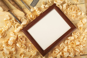 Blank frame on wooden background with sawdust.