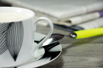 Eine Tasse Kaffee mit viel Milch und paar Zeitungem im Hintergrund