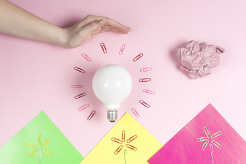 great idea concept with crumpled colorful paper and light bulb on light background. Creative brainstorm concept business idea.  female hand holding light bulb. Copy space for text.