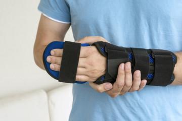 Mann hält seinen Arm in einer orthopädischen Schiene
