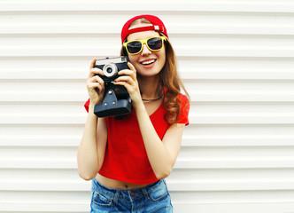Fashion pretty smiling woman with retro camera having fun over w