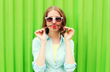 Woman having fun shows moustache hair over green background