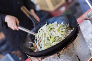 Cheff cooking traditional Thai noodles, Pad Thai, on street stall on international street food festival of Odprta kuhna, Open kitchen event, in Ljubljana, Slovenia.