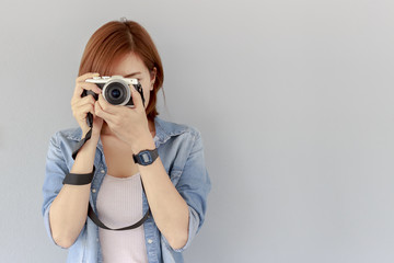 Photographer girl shooting images with brick wall, copy space area