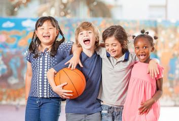 Elementary school children happy playing basketball at school