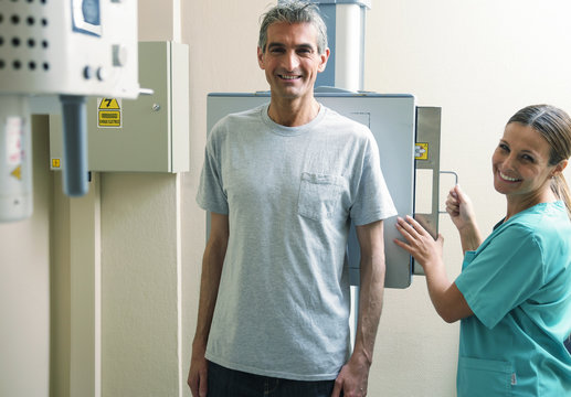 Happy female doctor ready to screen male patient at xray machine
