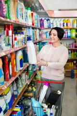 Woman choosing washing detergent in household department