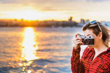 girl posing with retro camera at sunset