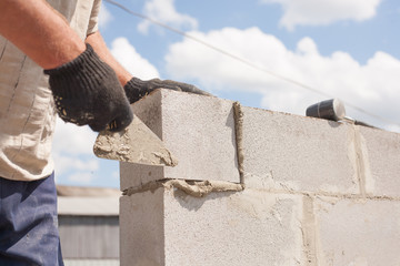 worker aligns with a spatula, lay brick cinder blocks