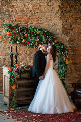 A loving groom kissing his smiling bride in her neck,she's embracing him gently, flowered brick wall on the back