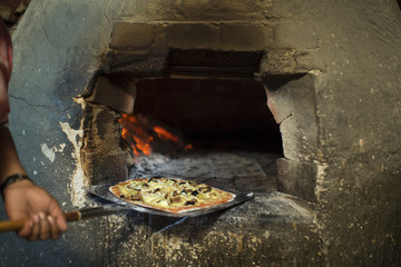 Pizza baker taking pizza out of pizza oven