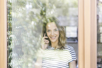 Portrait of smiling woman on cell phone behind windowpane