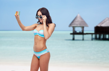 woman in bikini taking smatphone selfie on beach