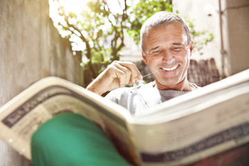 Portrait of smiling man reading newspaper Wall mural