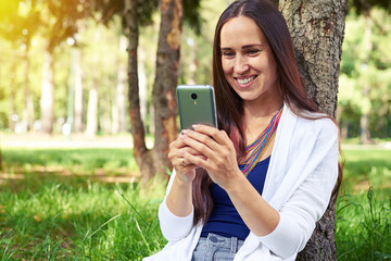 Smiling woman sitting under tree and using smart phone