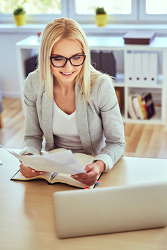 Happy woman working with laptop and financial documents from hom