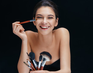 Happy girl makes herself make up. Photo of brunette girl with brushes for make up on black background