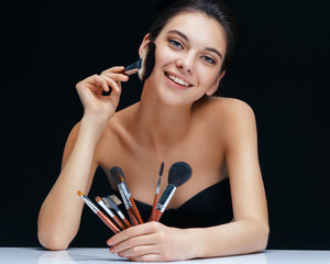 Charming young woman with brushes make up. Image girl on black background. Youth and skin care concept