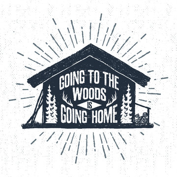 """Hand drawn label with textured wooden cabin vector illustration and """"Going to the woods is going home"""" lettering."""