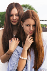 Two Redhead Teen Sisters in the Street Having Fun