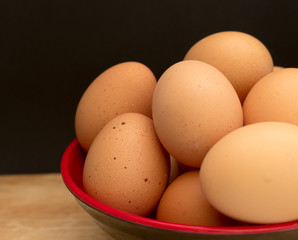 An eggs in a bowl on wooden board and black background