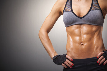 Cropped image of female model with muscular body