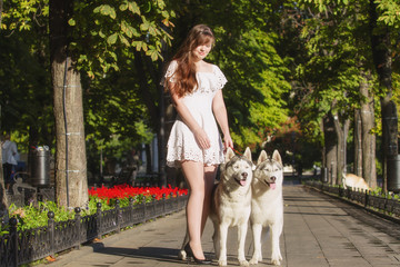 oung girl walking down the street with two dogs. A girl in a white dress. Siberian Huskies.