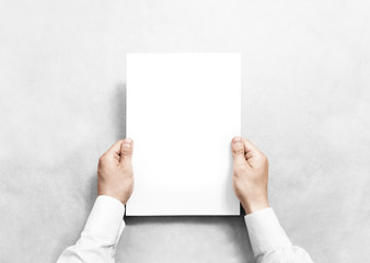Hand holding white blank paper sheet mockup, isolated. Arm in shirt hold clear brochure template mock up. Leaflet document surface design. Simple pure print display show. Reading contract agreement.