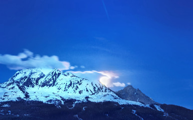 lune derrière nuage au dessus des montagnes