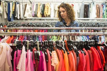 Female Shopper In Thrift Store browsing through colourful  dresses