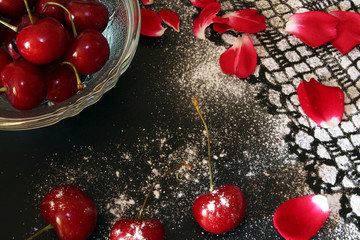 Sweet cherry against black background,  lacy drawing from icing
