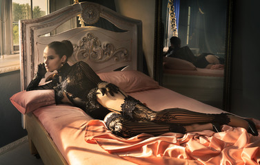 Girl lying in bed, her fashionable lingerie