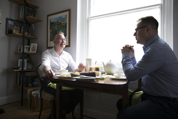 Male Homosexual Couple Eating Meal At Table
