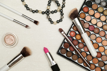 Make up set on light silver background. Eyeshadow palette, brushes and lipstick.