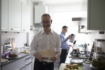 Male Homosexual Couple Preparing Meal In Kitchen