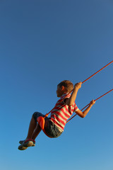 Little boy on a swing against blue sky. Background with copy space