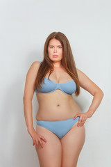Portrait of beautiful fat woman in lingerie or underwear posing in studio. Red haired lady posing with her hand on hip.