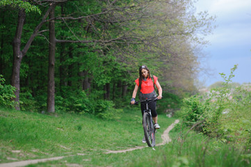 Girl riding a bike in the woods