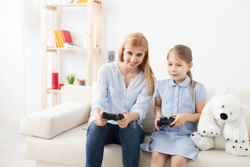 Mother and daughter playing on console