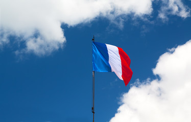French flag in blue sky - French national flag on wind among white clouds