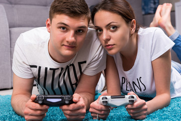 Young attractive pair lying on a rug playing video games