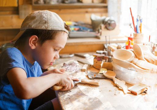 boy learning wood carving. young carpenter working in a workshop