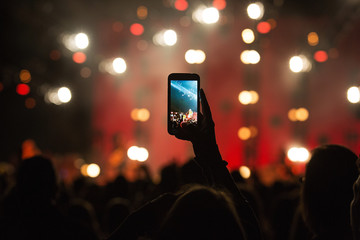 fan taking photo with cell phone at a concert