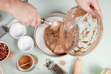 closeup hand transferring cake mixture cake pan