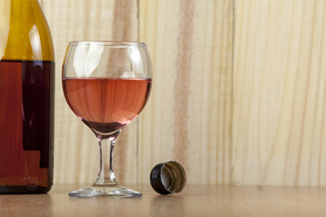 Glass and a bottle of red wine on wooden background