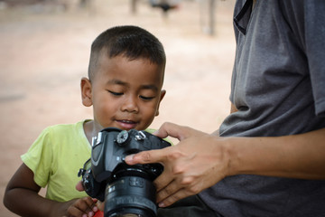 smiling child and smart photographer looking photos in camera at old home